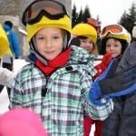 Sárga sisakhuzatos gyerekek a sípályán