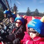 Síelő gyerekek a felvonóban kék sisakhuzatban