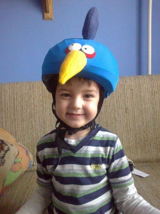 Vidám kisfiú kék madár sisakhuzatban
